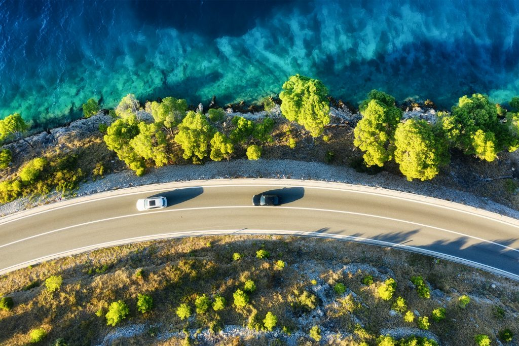 View of the road along the coast from the drone. Travel by car in summer time.